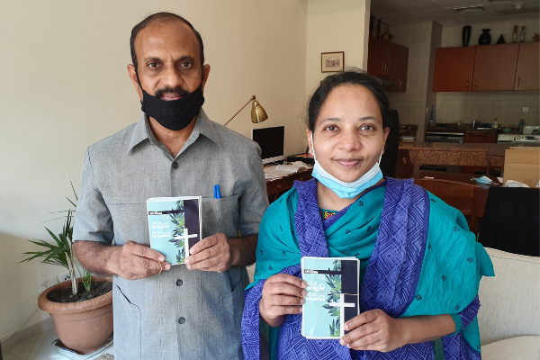 Two church leaders in the UAE with Scripture booklets for migrant workers.