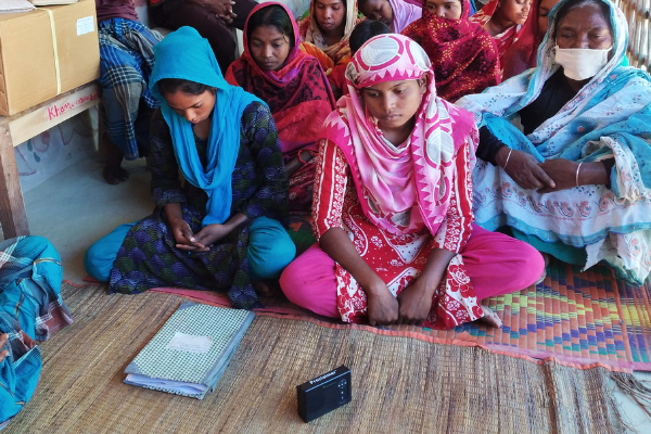 A group listening to an audio Bible during the pandemic.